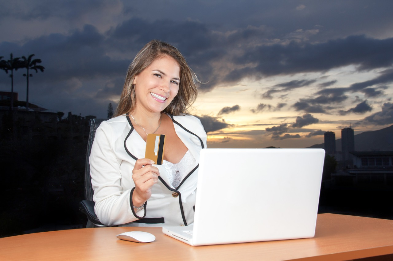 A person sitting at a table with a laptop and smiling at the camera